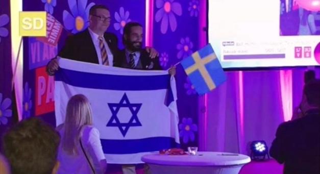 Bild från Sionistdemokraternas valvaka 2014. Många ledande partimedlemmar lät sig gladeligen fotas bakom den stora israeliska flaggan. Att den svenska flaggan är så mycket mindre än den israeliska ger oss en ouppsåtlig symbolik över det verkliga maktförhållandet i partiet.